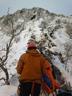 雪庇のある雪稜の奥に控える第二岩峰を仰ぎ見る